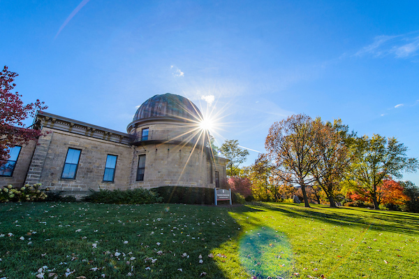 Washburn Observatory on a grassy green hill in front of a sunny, blue sky.