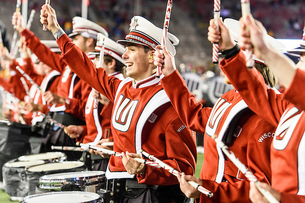 A row of drummers in marching band uniform smile to the crowd.